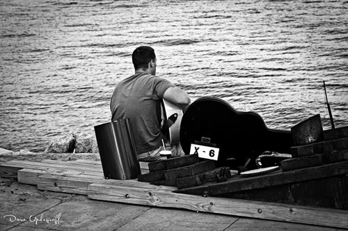 Strumming his guitar